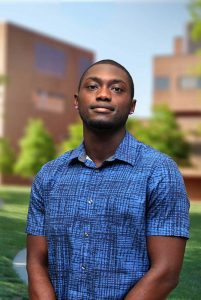 A three quarter portrait of Kojo on the Library green.