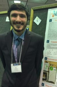 A head and shoulders image of Avi in front of his presentation board.