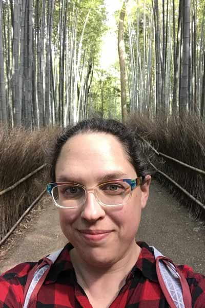An informal portrait of Meredith Power on a (walking) bridge, in the woods